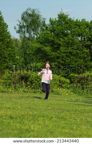 Adorable happy little girl running on green grass with developing long hair in a summer park - stock photo