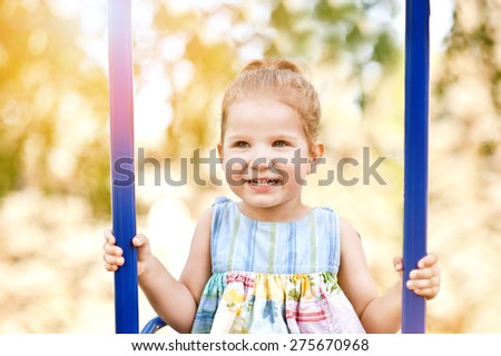 Adorable happy little girl smiling on swing on a sunny summer playground in a park.