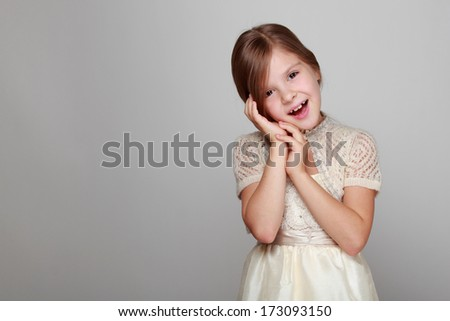 Adorable happy little girl with long hair in a fairy dress on a gray background on Holiday - stock photo