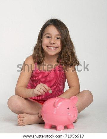 Adorable happy little girl with piggy bank