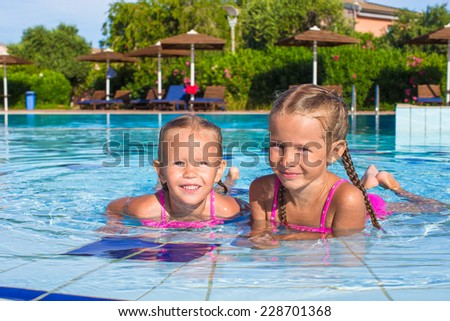 Adorable happy little girls having fun in the swimming pool