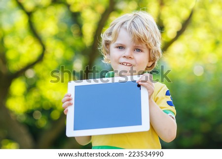 Adorable happy little kid boy holding tablet pc, outdoors. Toddler child learning with modern technology. - stock photo