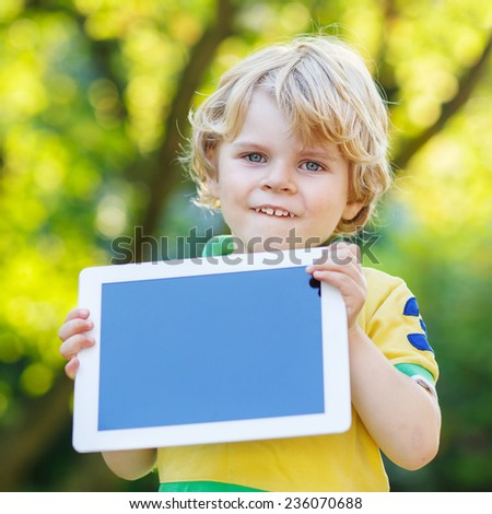 Adorable happy little kid boy holding tablet pc, outdoors. Toddler child learning with modern technology. Square format. - stock photo