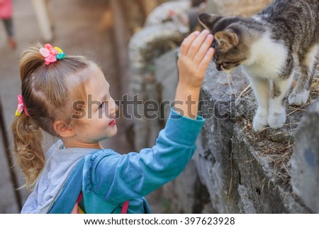 Adorable happy little kid girl petting a cat outdoors - stock photo