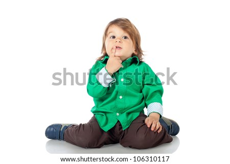 Adorable happy little kid, 2 years old boy, sitting on the floor gesturing a kiss or a secret, wearing shirt and jeans. High resolution image isolated on white background with copy space. Studio shot.
