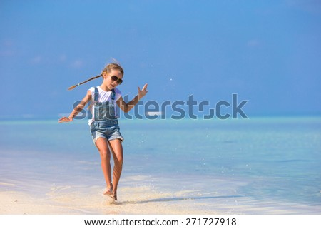Adorable happy smiling little girl have fun on beach vacation - stock photo