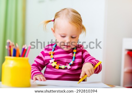 Adorable happy toddler girl drawing with coloring pencils at home or daycare, perfect for early education context - stock photo