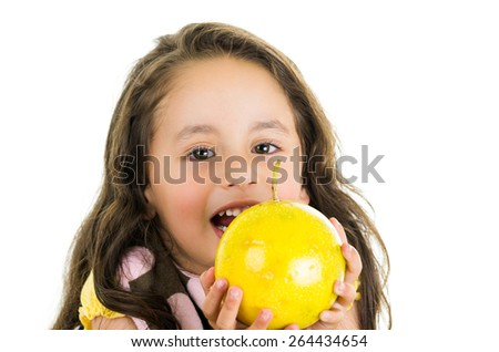 Adorable healthy little girl holding a passionfruit in front of her face isolated on white - stock photo