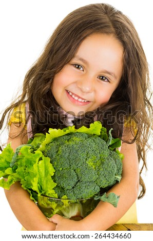 Adorable healthy little girl holding salad bowl with broccoli and lettuce isolated on white - stock photo