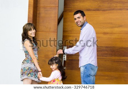 Adorable hispanic family of three posing for camera outside front entrance door while entering house. - stock photo