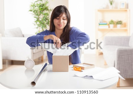 Adorable Hispanic woman wrapping gift with silver wrapping paper and brown box  in living room at table wearing blue shirt. - stock photo