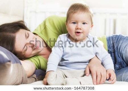 Adorable joyful baby boy sitting in bed next to his mother while she is embracing him lying down and looking at him. - stock photo
