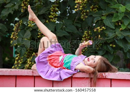 Adorable joyful little girl in a bright summer dress eating ice cream in a park in sunny summer day