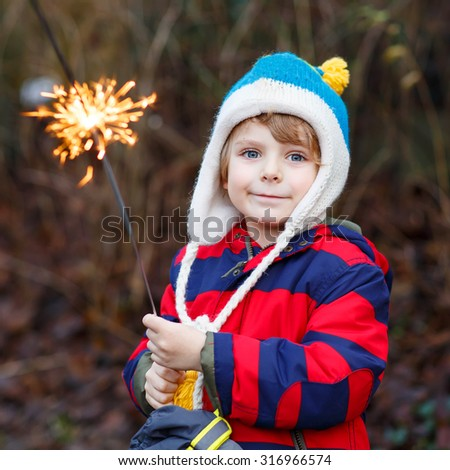 Adorable kid boy in winter clothes holding burning sparkler on New Year's Eve. Safe fireworks for kids concept. Happy child having fun outdoors. - stock photo