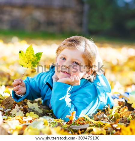 Adorable kid boy laying with a lot of yellow autumn leaves in park. Kid boy having fun on sunny warm october day. Season, children, lifestyle concept