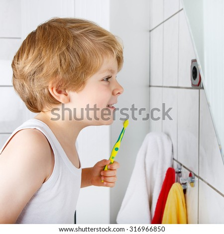Adorable kid boy learning brushing his teeth in domestic bath. Child learning how to stay healthy. Health care concept. - stock photo