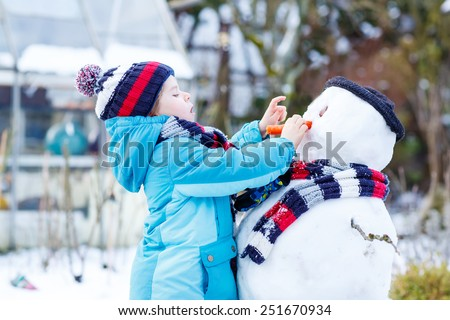 Adorable kid boy making a snowman and eating carrot, playing and having fun with snow, outdoors  on cold day. Active outoors leisure with children in winter. - stock photo
