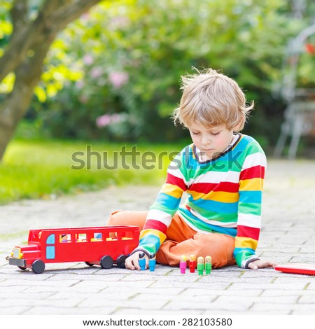 Adorable kid boy of 4 years playing with wooden red school bus and toys in summer garden. Leisure with children, outdoors. - stock photo