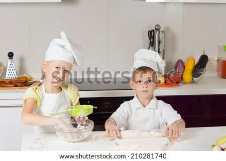 Adorable Kid Chefs Baking Something to Eat in the Kitchen. - stock photo