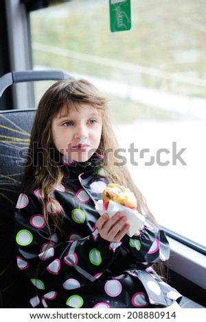 Adorable kid girl eating powder muffin inside the bus - stock photo