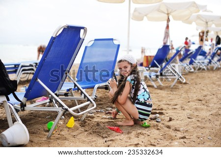 Adorable kid girl  girl  playing with sand  on the beach. - stock photo