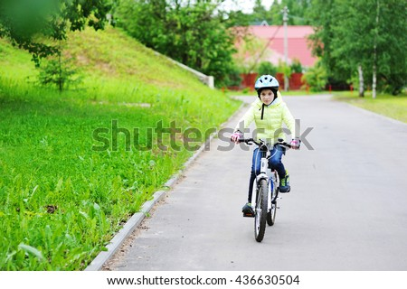 Adorable kid girl in blue helmet and jacket riding on bicycle in the town. - stock photo