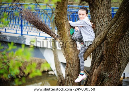 Adorable kid girl in grey outfit has fun in the spring park - stock photo