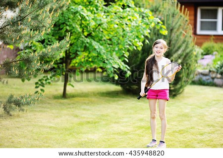 Adorable kid girl in pink shorta playing badminton outdoor - stock photo