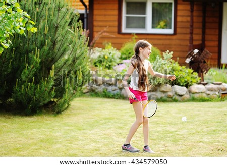 Adorable kid girl in pink shorts playing badminton outdoor - stock photo