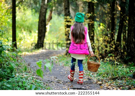Adorable kid girl in pink vest, white sweater, green hat and boots with basket picking mushrooms in autumn forest at sunny day - stock photo