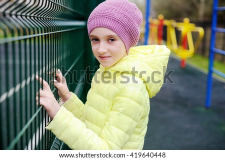 Adorable kid girl in the hat and jacket standing near  the school  stadium - stock photo