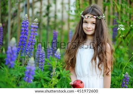 Adorable kid girl in white summer dress in the field of the beautiful lupines - stock photo