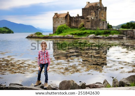 Adorable kid girl on the scenic view of old Scotland castle and lake during hiking walk. Eilean Donan Castle. - stock photo