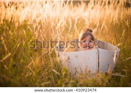 Adorable kid girl seaman floats on a sailing boat in the field at sunset on a warm evening summer. Dreams of travel! Child floats on a handmade boat against the backdrop of a sunset. - stock photo