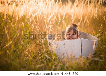 Adorable kid girl seaman floats on a sailing boat in the field at sunset on a warm evening summer. Dreams of travel! Child floats on a handmade boat against the backdrop of a sunset.