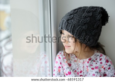 Adorable kid girl with big eyes in dark grey knit hat near the window - stock photo