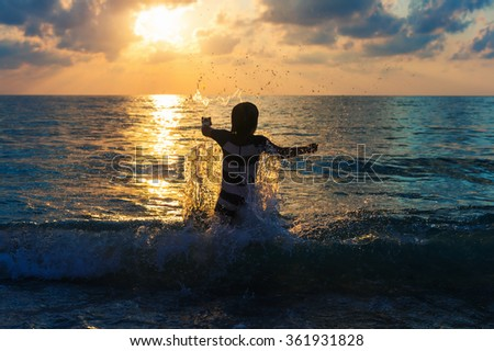 Adorable kid having fun on summer vacation at sunset, playing in the sea, image taken in Tropea, Calabria, Italy - stock photo