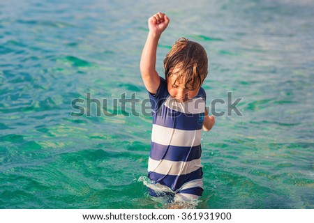 Adorable kid having fun on summer vacation, playing in the sea, image taken in Tropea, Calabria, Italy - stock photo