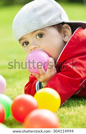 Adorable kid playing and biting ball
