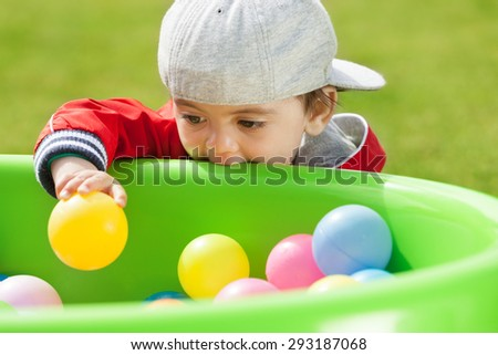 Adorable kid playing and biting playground - stock photo