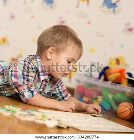 Adorable kid playing in a room with his toys. He is young designer with many ideas waiting to be found. Very shallow depth of field. - stock photo