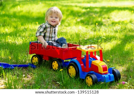 Adorable kid playing in the garden sitting in the trailer of his colorful toy truck