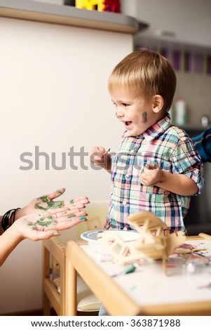 Adorable kid playing on his table with watercolors all over the face. He is young artist with many ideas waiting to be found. Very shallow depth of field. - stock photo