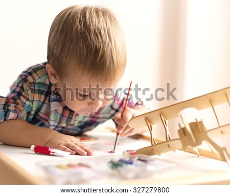 Adorable kid playing on his table with watercolors, painting a wooden parts of his airplane wooden toy. He is young designer with many ideas waiting to be found. Very shallow depth of field. - stock photo
