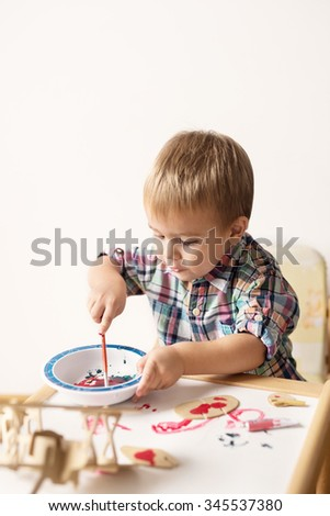 Adorable kid playing on his table with watercolors, painting a wooden parts of his airplane wooden toy. He is young designer with many ideas waiting to be found. Shallow depth of field. - stock photo