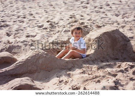 Adorable kid, playing on the beach, sitting in a ferrari car, made of sand, smiling at the camera, pretending to drive - stock photo