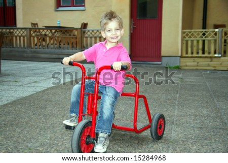 Adorable kid riding a tricycle (Shallow DOF)