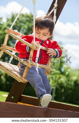 Adorable kid swinging outdoors on the sunny day