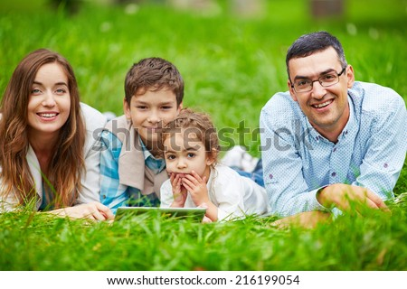 Adorable kids and their parents spending leisure outdoors - stock photo