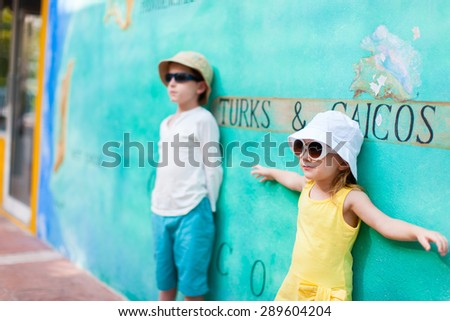 Adorable kids outdoors against colorful wall on summer day - stock photo